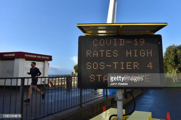 "Member of public jogs past a public safety notice that reads ""Covid-19 Rates High, SOS-Tier 4, Stay Safe"" on the promenade on December 20, 2020 in..."