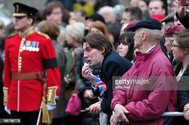 A member of public reacts as the coffin containing late British Prime Minister Baroness Margaret Thatcher is taken from St Clement Danes church...
