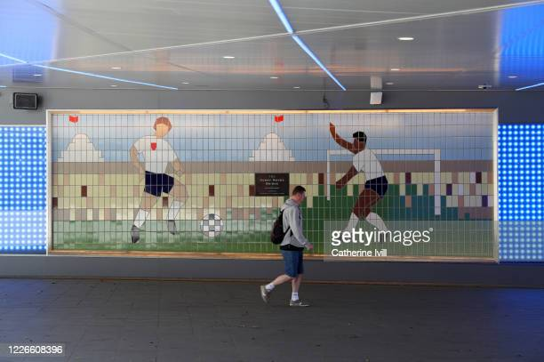 Member of public walks past a mural under the Bobby Moore bridge close to Wembley stadium on May 23, 2020 in London, England. The British government...
