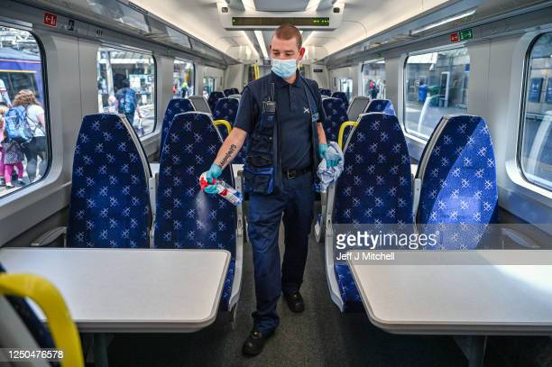 Member of railway staff cleans a train at Waverley Station on June 18, 2020 in Edinburgh, Scotland. First Minister Nicola Sturgeon announced phase 2...