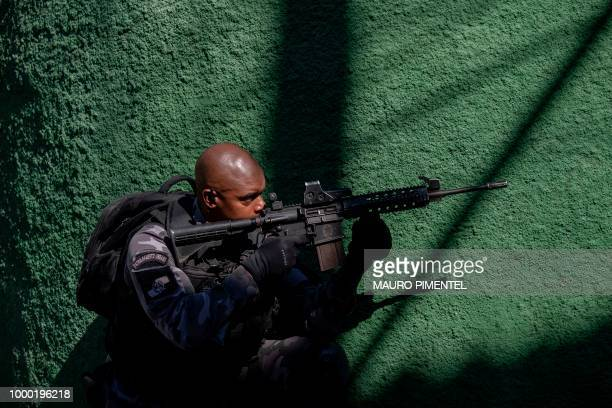 A member of Rio de Janeiro's Military Police Special Unit takes position during an operation at the Complex do Alemao favela in Rio Brazil on July 16...