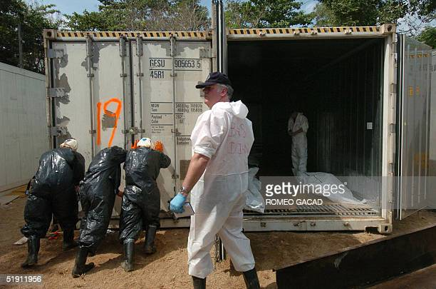 Member of Royal Netherlands Police waits for more bodies of tsunami victims while Thai volunteers seals a refrigirated container van at the Yan Yaw...