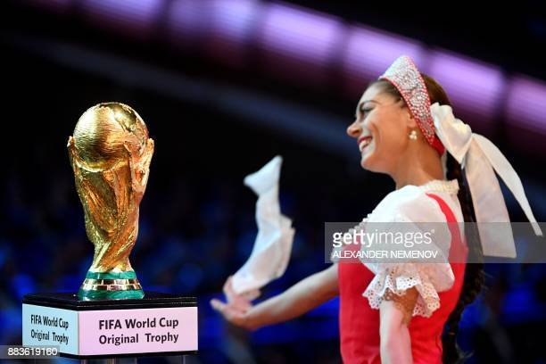 A member of Russia's Igor Moiseyev Ballet ensemble dances next to the FIFA World Cup trophy ahead of the 2018 FIFA World Cup football tournament...