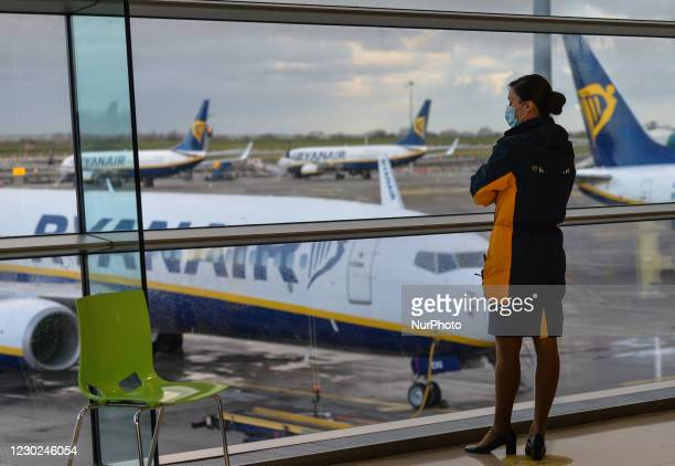 Member of Ryanair cabin crew looks out of the window at Ryanair planes grounded at Dublin Airport . From midnight all flights and passenger ferries...