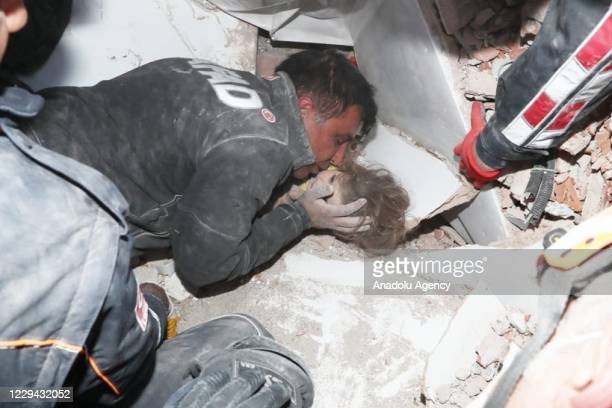 Member of search and rescue team kisses 4-year-old Ayda Gezgin on the cheek as she under the debris of a building before pulling her out 91 hours...