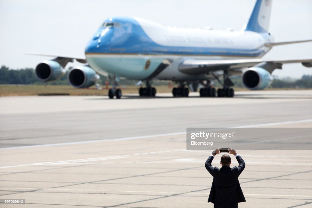 A member of security detail takes a smartphone picture as Air Force One taxis on the tarmac at London Stansted Airport in Stansted, U.K., on Thursday, July 12, 2018. U.S. President Donald Trump will avoid London as much as possible as he's whisked off on a tour of prime British real estate to keep him away from protesters during his U.K. visit. Photographer: Chris Ratcliffe/Bloomberg via Getty Images