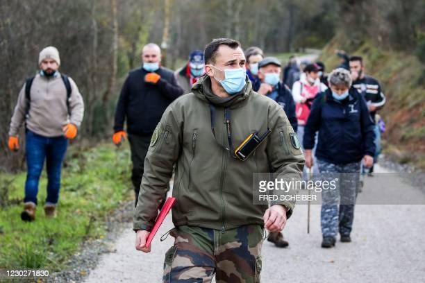 Member of security forces leads a group of people during a search organised by French gendarmes in the woods of Milhars, on December 23 to look for...
