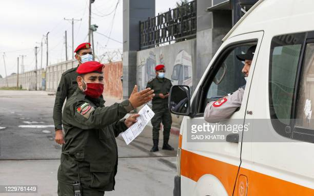 A member of security forces loyal Gaza rulers Hamas motions to an ambulance at the Rafah border crossing between the Gaza Strip and Egypt on November...