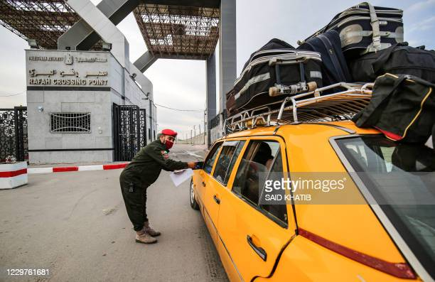 A member of security forces loyal Gaza rulers Hamas speaks with the driver of a vehicle waiting to cross onto the Egyptian side at the Rafah border...