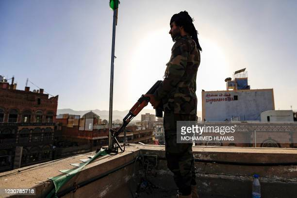 Member of security forces loyal to Yemen's Huthi rebels stands guard as supporters attend a rally denouncing the United States and the outgoing Trump...