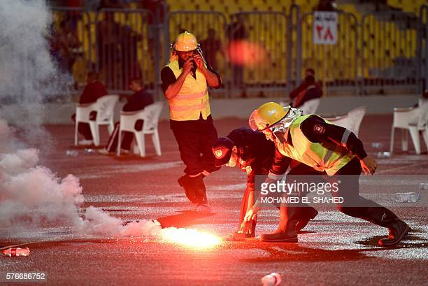 A member of security removes a flare thrown by fans during their CAF Champions League group A stage football match between Egypt's AlAhly and...
