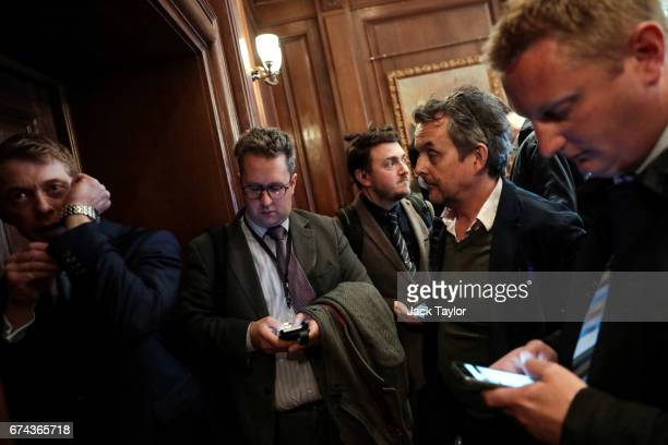 A member of security speaks into a microphone as journalists wait outside a room to speak to UKIP Leader Paul Nuttall following his speech as the...