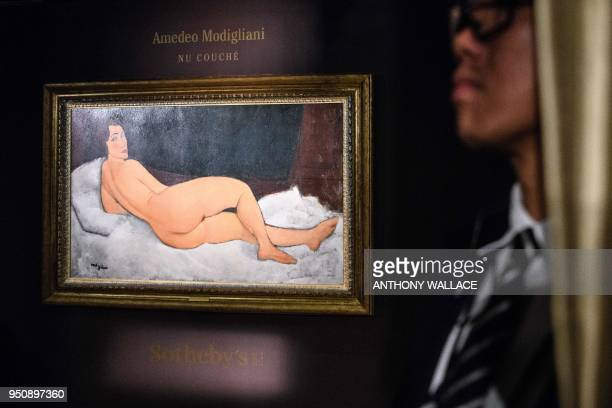 A member of security stands guard after Italian painter and sculptor Amedeo Clemente Modigliani's 'Nu couché ' painting is unveiled at the Sothebys...