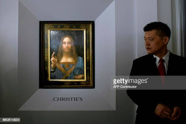 A member of security stands guard next to Leonardo da Vinci's 'Salvator Mundi' painting after it was unveiled in Hong Kong on October 13 2017 / AFP...