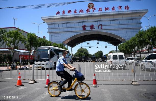 A member of security wearing a face mask cycles past the closed Xinfadi Market in Beijing on June 14 2020 The domestic COVID19 coronavirus outbreak...