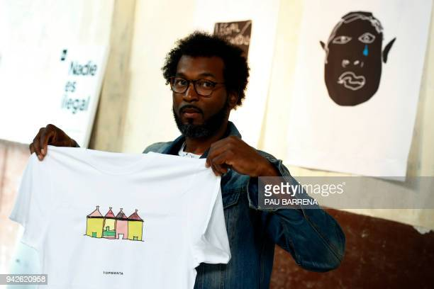 Member of 'Sindicato Popular de Vendedores Ambulantes' Senegalese vendor Mouhamed shows a tshirt of their new crowdfunded trademark project 'Top...
