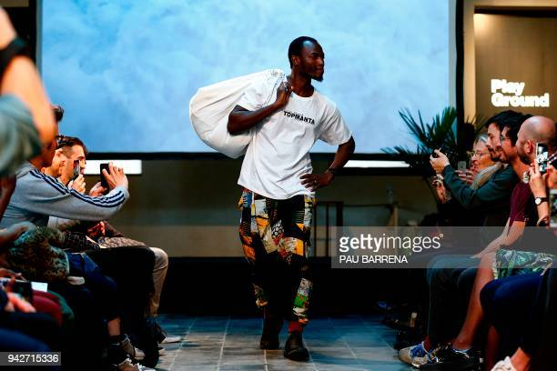 A member of 'Sindicato Popular de Vendedores Ambulantes' walks the catwalk during a fashion show to present the tshirts of their new crowdfunded...