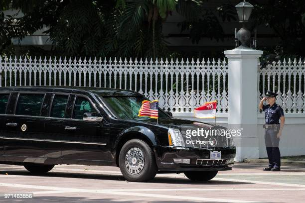 A member of Singapore Police Force salutes US President Donald Trump's motorcade as it exits the Istana presidential residence in Singapore on June...