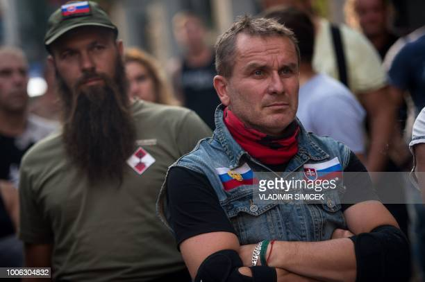 A member of Slovak Defenders and a motorcycle rider with Russian and Slovak flag on his jacket attend a rally for Russia's motorcycle club Night...
