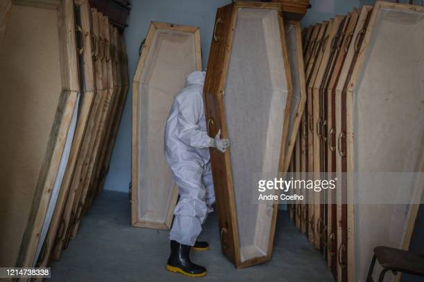 Member of SOS Funeral wearing a personal protective equipment holds an empty coffin at the team base deposit, on May 22 2020 in Manaus, Brazil. SOS...