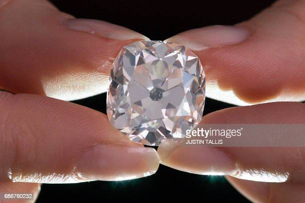 A member of Sotheby's staff poses holding a 2627 carat cushionshaped white diamond for sale at Sotheby's auction house in London on May 22 2017 The...