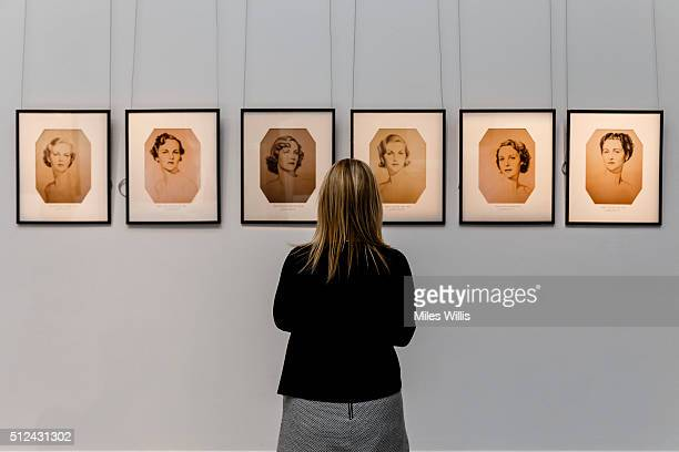 Member of Sotheby's staff poses with six portraits of the Mitford sisters, after William Acton during a behind the scenes look at the personal...
