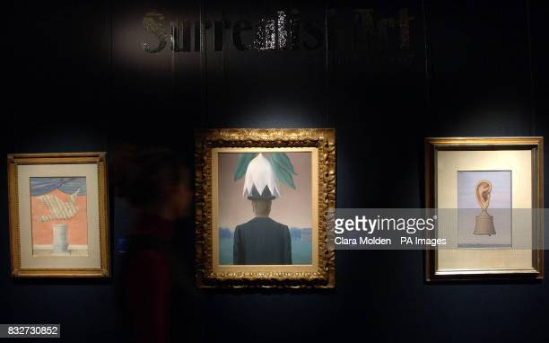 A member of Sothebys staff walks past three paintings by Rene Magritte one of which 'L'Okapi' is expected to reach between 2535 million when it's...