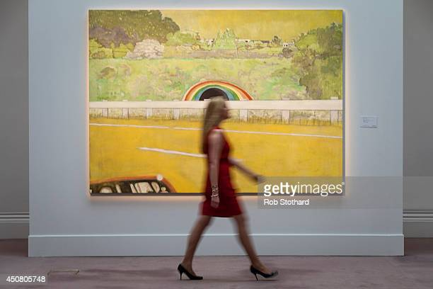A member of Sotheby's walks in front of Peter Doig's 1999 piece CountryRock estimated to sell for £9 million on display at Sotheby's auction house on...
