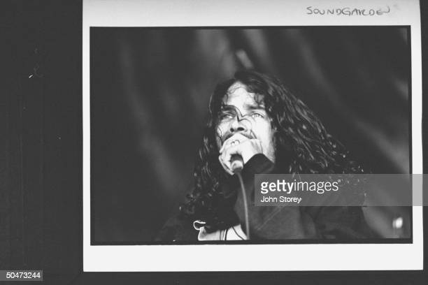 Member of Soundgarden rock group Chris Cornell holding mike as he sings on stage during the Lollapalooza '92 traveling rock fest cum carnival