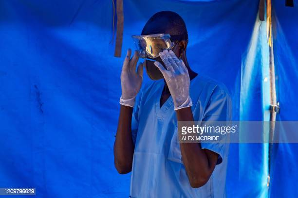 Member of South Sudanese Ministry of Health's Rapid Response Team puts on the eye protection before taking a sample from a man who has recently been...