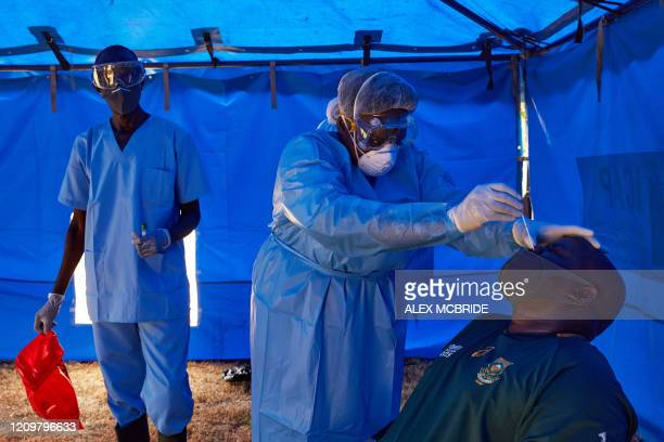 Member of South Sudanese Ministry of Health's Rapid Response Team take a sample from a man who has recently been in contact with a confirmed case of...