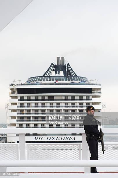 A member of Spanish Guardia Civil stands guard while MSC Splendida cruise ship some of whose passengers were among the victims of a terrorist attack...