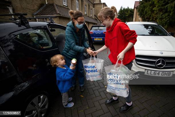 Member of staff accepts bags of food donatons at the Cooking Champions food bank in Grange Park, north London on October 27 during the novel...