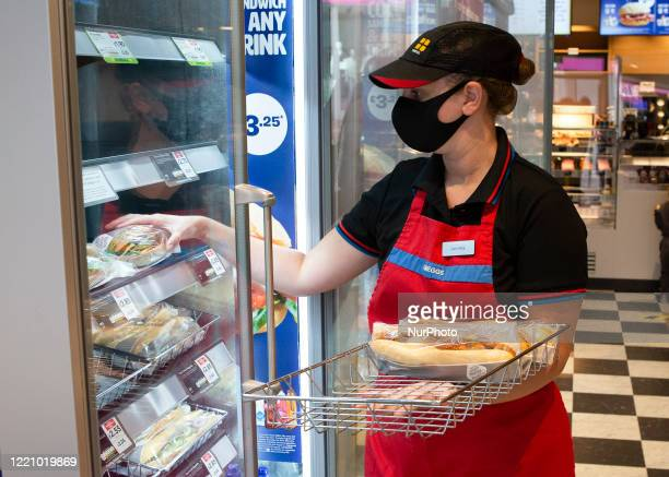 Member of staff adding more food to the shelves as Greggs bakery reopens 800 stores nationwide. Greggs closed all of their bakery's due to the...