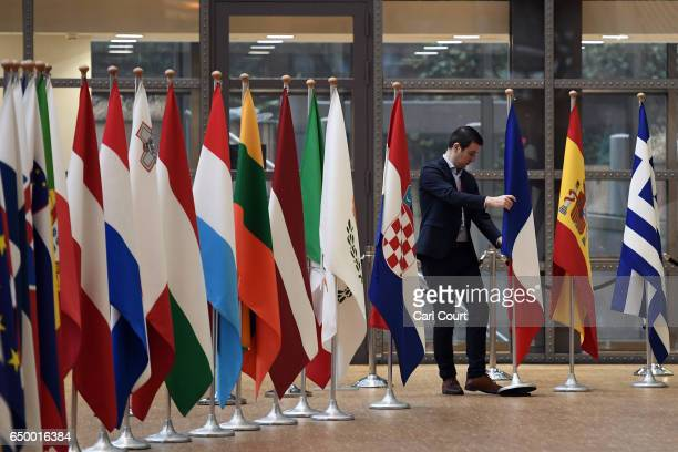 A member of staff adjusts flags in the arrival area of the Europa building at the Council of the European Union on the first day of an EU summit on...