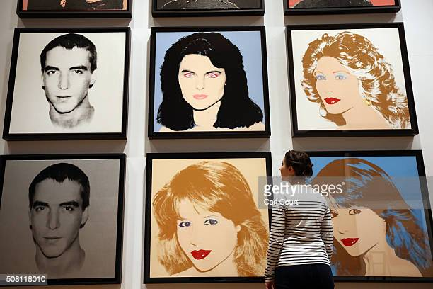 A member of staff and her child walk next to a series of artworks by Andy Warhol at the Ashmolean Museum on February 2 2016 in Oxford England The...
