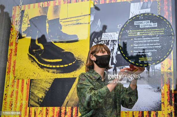 A member of staff applies a safety sign to the Dr Martens store window in Princess Street as the Scottish Lockdown eases and shops reopen on June 29...