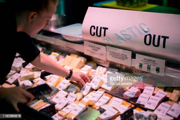 Member of staff arranges cheese in cellulose plastic-free packaging for sale at Budgens supermarket in Belsize Park, north London on July 2, 2019. -...