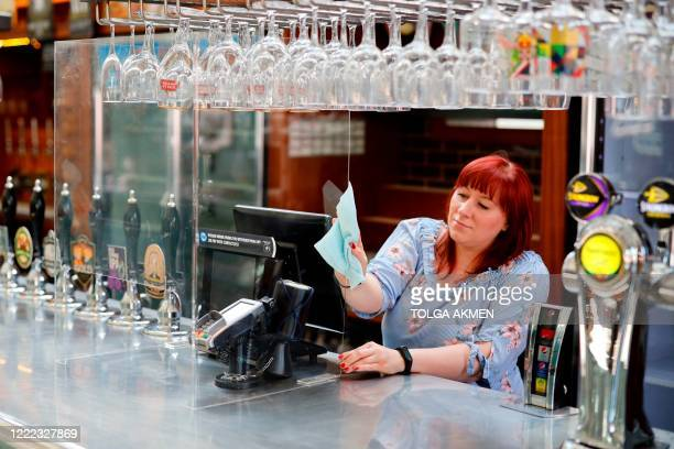 Member of staff at a Wetherspoons pub in north London cleans a perspex barrier put in place for pubs to reopen early next month on June 24, 2020. -...