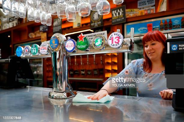 Member of staff at a Wetherspoons pub in north London cleans the bar in preparation for pubs to reopen early next month on June 24, 2020. - Prime...