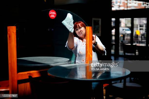 Member of staff at a Wetherspoons pub in north London cleans the partitions erected in preparation for pubs to reopen early next month on June 24,...