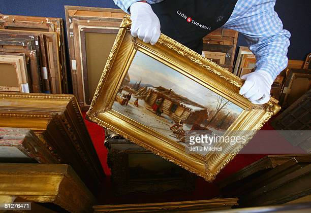 A member of staff at Lyon and Turnbull holds 'Chopping logs outside a snow covered cabin' a painting which was bought at Glasgow's Barras market 30...