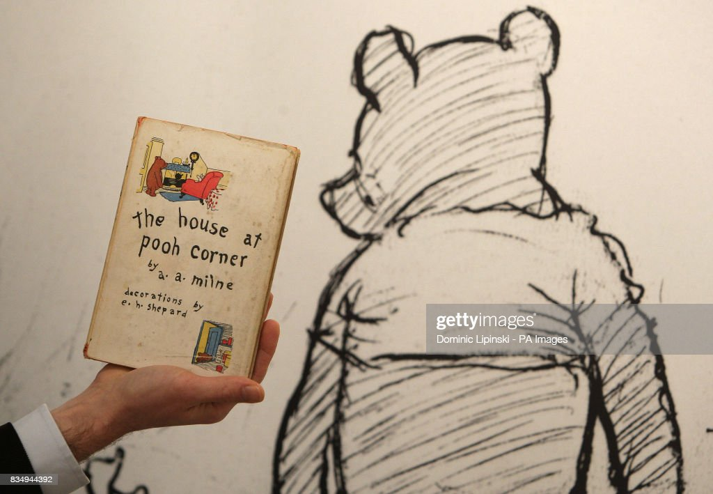 A member of staff at Sotheby's auction house holds a first American edition of 'The House at Pooh Corner', by AA Milne, dating from 1928, part of a collection of Winnie the Pooh illustrations and books which will be sold at auction on 17th December.