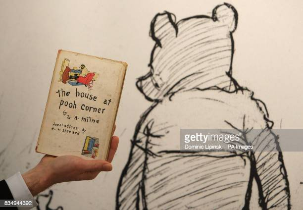 A member of staff at Sotheby's auction house holds a first American edition of 'The House at Pooh Corner' by AA Milne dating from 1928 part of a...