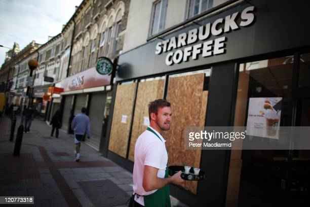 A member of staff at Starbucks stands outside the partly boarded up cafe to offer free drinks to passersby in Clapham Junction on August 10 2011 in...