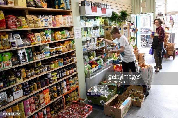 Member of staff at the community owned grocery shop, The Village Green, picks an emailed order from a local resident self-isolating amidst the novel...