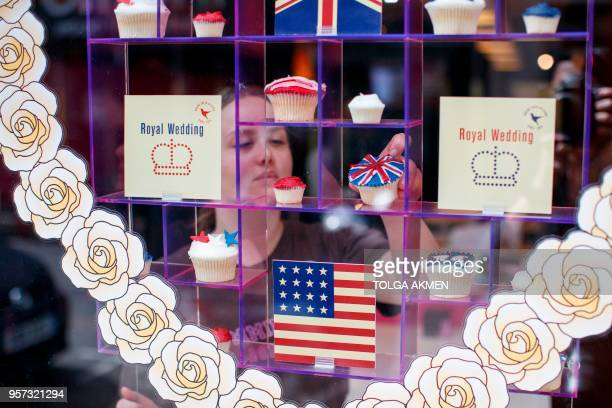 Member of staff at the Hummingbird Bakery poses the window display of cupcakes themed with icing depicting the Union Flag, the US flag, stars and...