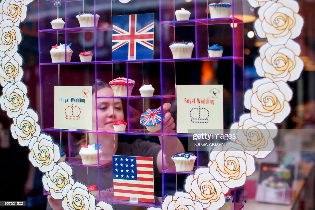 A member of staff at the Hummingbird Bakery poses the window display of cupcakes themed with icing depicting the Union Flag, the US flag, stars and crowns to mark the upcoming Royal Wedding of Prince Harry and US actress Meghan Markle in central London on May 11, 2018.