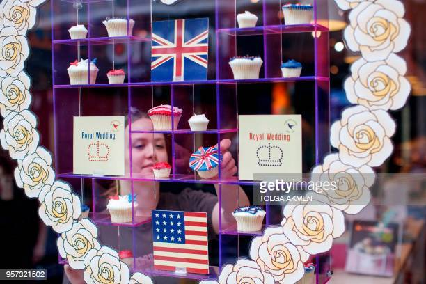A member of staff at the Hummingbird Bakery poses the window display of cupcakes themed with icing depicting the Union Flag the US flag stars and...