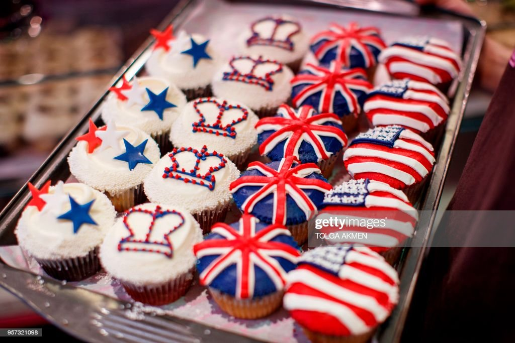 A member of staff at the Hummingbird Bakery poses with cupcakes themed with icing depicting the Union Flag, the US flag, stars and crowns to mark the upcoming Royal Wedding of Prince Harry and US actress Meghan Markle in central London on May 11, 2018.